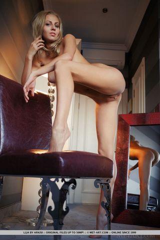 Модель на кожаном стуле позирует в голом виде и возбуждается