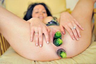 Сисястая девка в майке пихает несколько цукини в анус и промежность