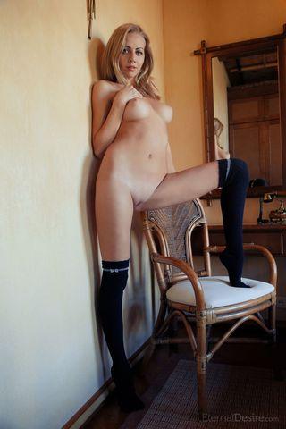 Девка с длинными ногами в черных чулках сидит на трюмо и светит вагиной