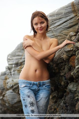 Туристка на скалистом побережье работает голая перед камерой друга