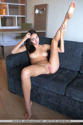 Гибкая брюнетка на диване поднимает ногу и разминает бритую вагину