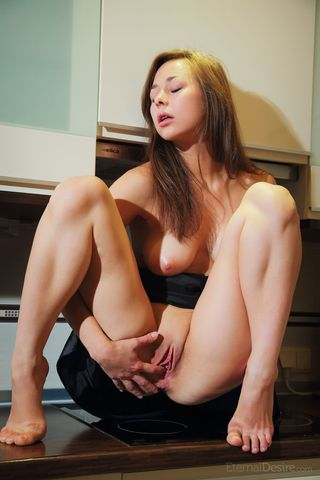 Девушка лежит на кухонном столе и пихает два пальчика в промежность