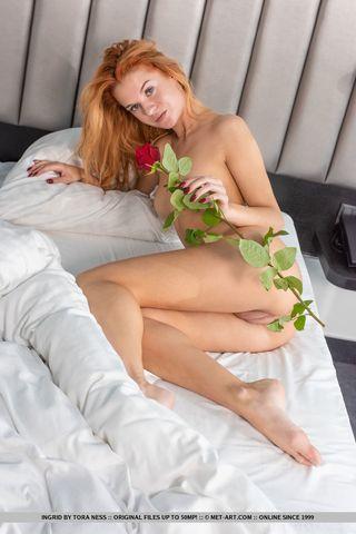 Рыжая с букетом роз позирует перед камерой без трусиков и лифчика
