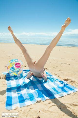 Нудистка на пляже на покрывале красиво показывает сочные сисечки